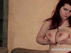 Mature hoe rubs huge tits in close-up